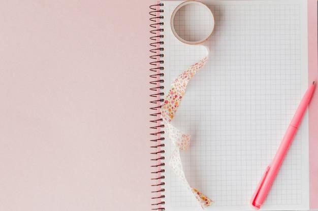 Retour à l'école. cahier, étui à crayons avec stylo et crayons sur rose