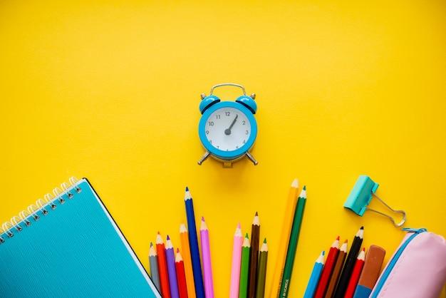 Retour à l'école coloré poser plat. crayons bloc-notes clips réveil et porte-stylo.