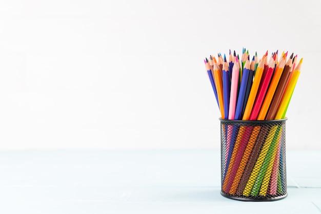 Retour à l'école concept, crayons colorés en boîte sur fond en bois blanc.