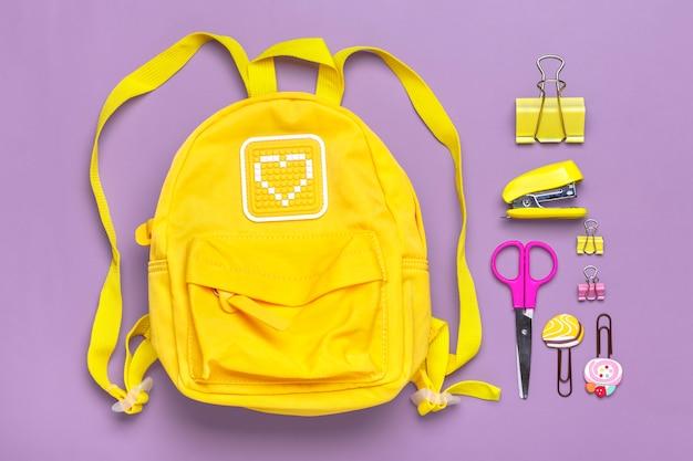 Retour à l'école, concept d'éducation. sac à dos jaune avec fournitures scolaires - cahier, stylos, clips, ciseaux isolés sur fond violet vue de dessus espace de copie composition à plat bannière