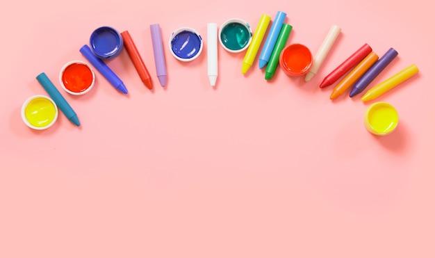 Retour à l'école. crayons de cire colorés, peintures pour créatif sur rose.