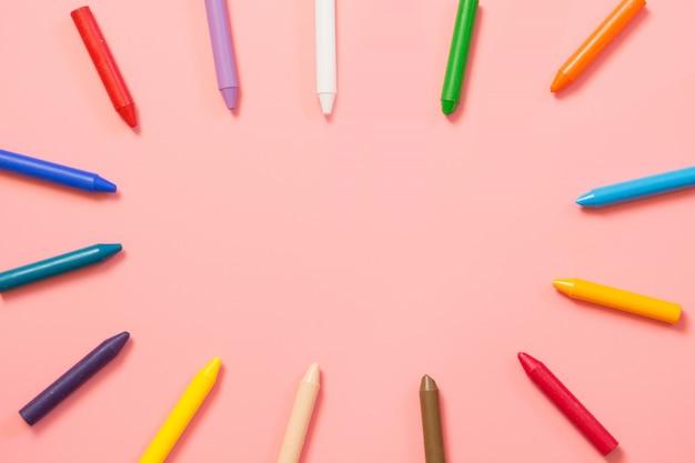 Retour à l'école. crayons de cire colorés sur rose.