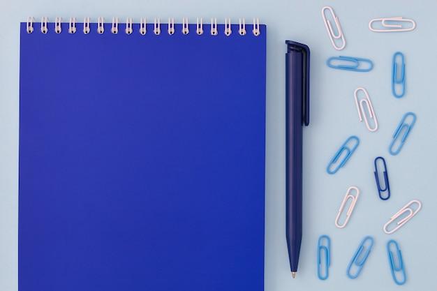 Retour à l'école créative. cahier bleu avec stylo et trombones sur une vue de dessus de fond bleu d'un plat poser.