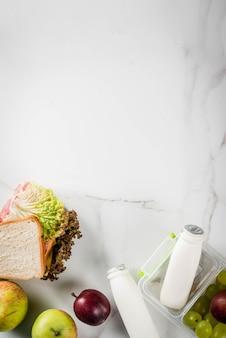 Retour à l'école. un déjeuner sain dans une boîte est composé de pommes de fruits frais, de prunes, de raisins, d'une bouteille de yaourt et d'un sandwich avec de la laitue, des tomates, du fromage et de la viande. table en marbre blanc. vue de dessus