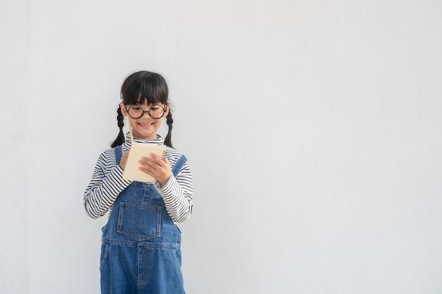 Retour à l'école. une drôle de petite fille dans des verres sur fond blanc. enfant de l'école primaire avec un livre.