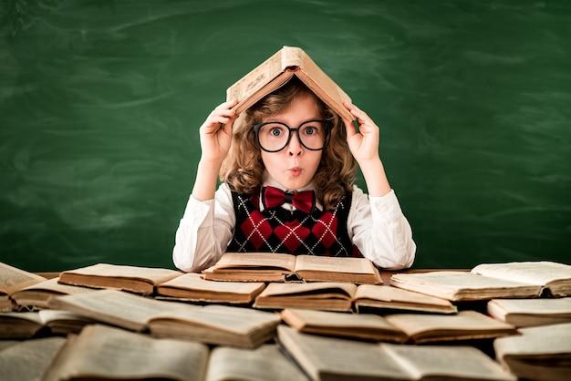 Retour à l'école écolier en classe enfant heureux contre le tableau vert éducation et créativité