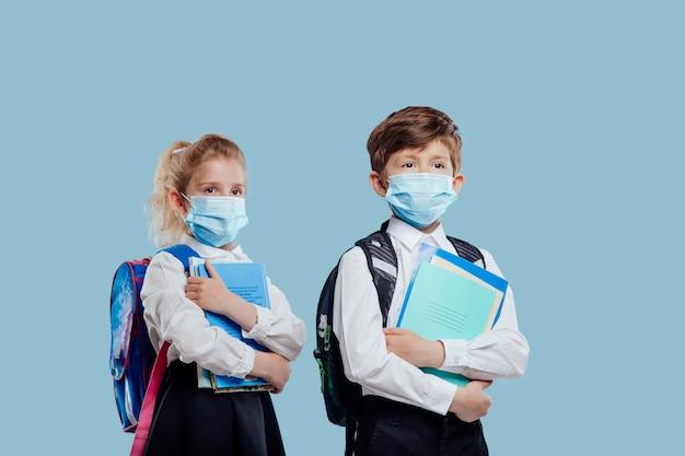 Retour à l'école écolier avec masque médical et sac à dos a des cahiers et des livres à la main isolés o ...