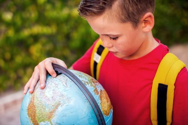 Retour à l'école. élève avec globe en plein air. concept de géographie et d'éducation