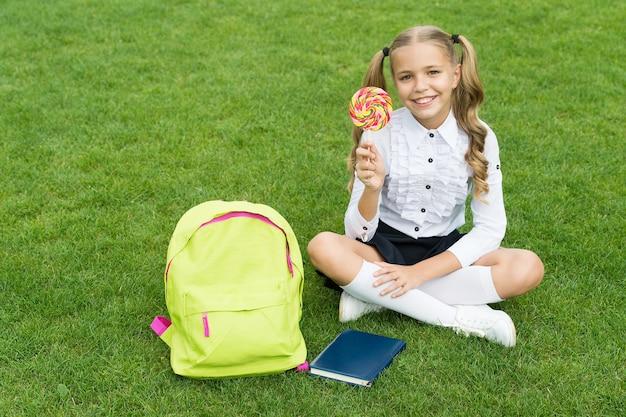 Retour à l'école enfant drôle tenir le concept de sucette de l'éducation journée d'apprentissage ordinaire jolie fille