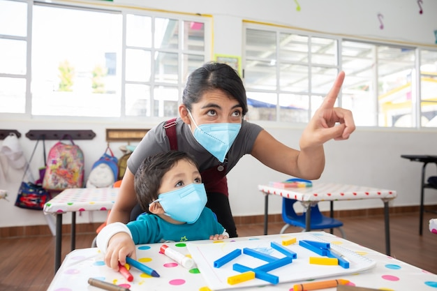 Retour à l'école enseignant et élève prenant des cours portant un masque facial après la pandémie de coronavirus