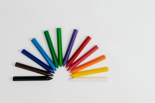 Retour à l'école. ensemble arc-en-ciel de couleurs crayon crayon crayon peinture isolée sur mur blanc