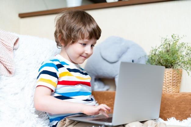 Retour à l'école. formation en ligne à distance. caucasien sourire enfant d'âge préscolaire garçon étudiant à