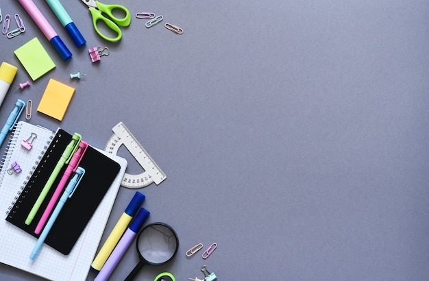 Retour à l'école. fournitures scolaires : cahier, stylo, crayon sur fond gris. vue d'en-haut. outils bureautiques.