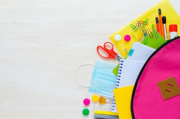 Retour à l'école fournitures scolaires colorées lumineuses et sac à dos pour l'école sur fond blanc