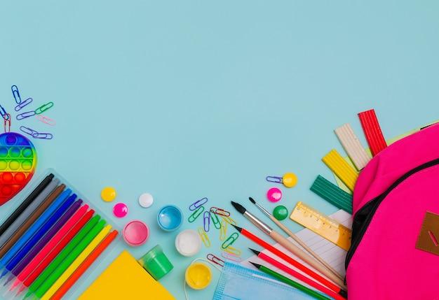 Retour à l'école fournitures scolaires colorées lumineuses et sac à dos pour l'école sur fond bleu