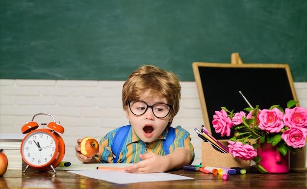 Retour à l'école garçon confus dans des verres devoirs leçons matières scolaires concept d'éducation nerd