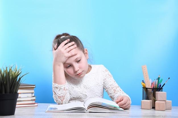 Retour à l'école. heureux enfant industrieux mignon est assis à un bureau à l'intérieur. l'enfant apprend en classe.