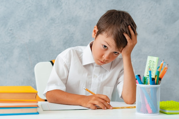 Retour à l'école. heureux étudiant souriant dessine au bureau.