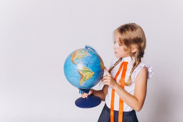 Retour à l'école. jolie fille blonde adorable caucasienne avec globe en uniforme scolaire sur fond blanc