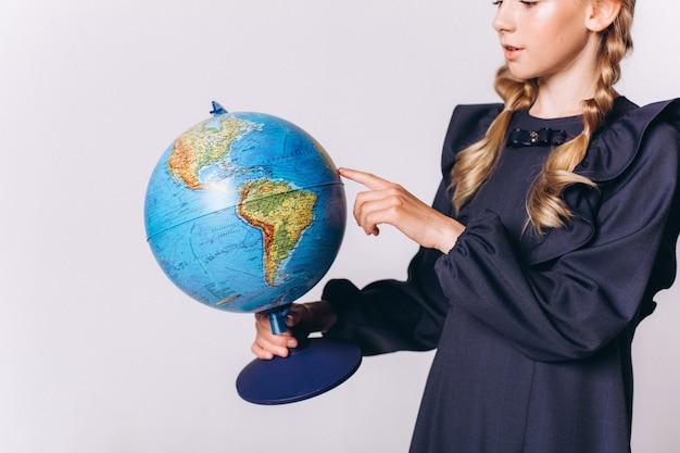 Retour à l'école. jolie fille blonde adorable caucasienne en uniforme scolaire avec globe sur fond blanc