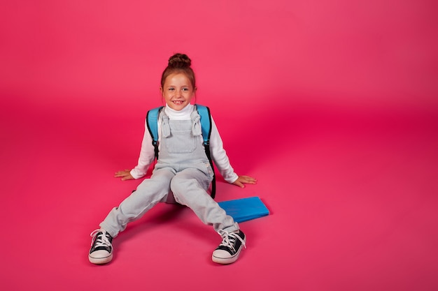 Retour à l'école. joyeuse fille heureuse avec un sac à dos bleu sur fond rose.