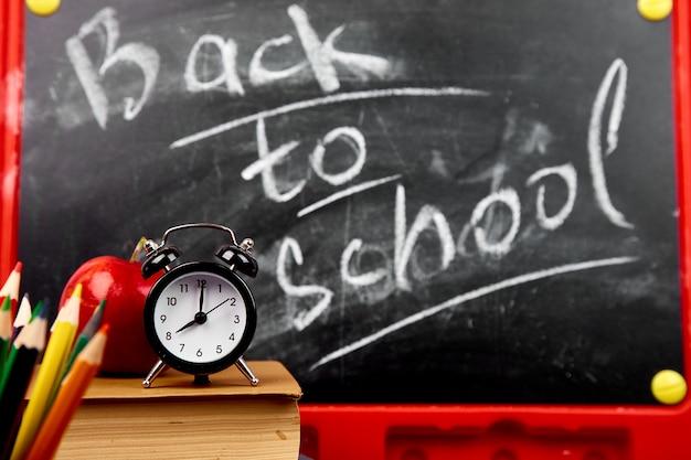 Retour à l'école lettrage sur tableau noir avec un morceau de craie