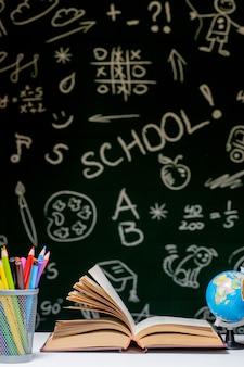 Retour à l'école avec des livres, crayons et globe sur tableau blanc sur tableau noir vert