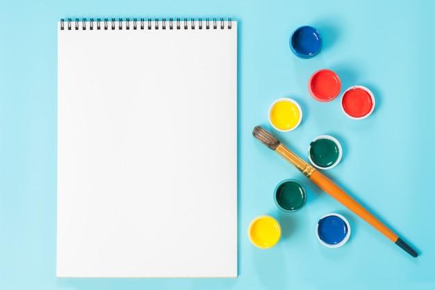 Retour à l'école. peintures colorées, album et pinceau sur bleu percutant. espace de copie. vue de dessus.