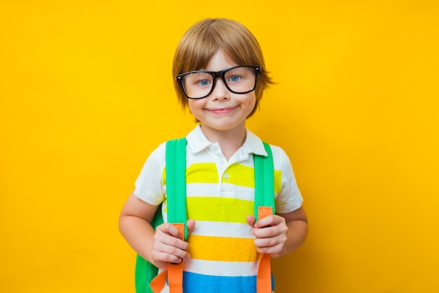 Retour à l'école. petit garçon à lunettes avec sac
