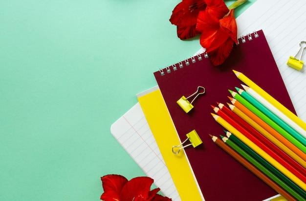 Retour à l'école à plat. divers articles de papeterie avec des fleurs sur une table à la menthe.