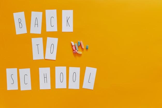 Retour à l'école à plat sur fond orange. lettres sur des autocollants.