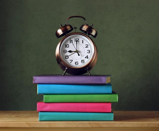 Retour à l'école. réveil et manuels scolaires en couvertures colorées sur la table.