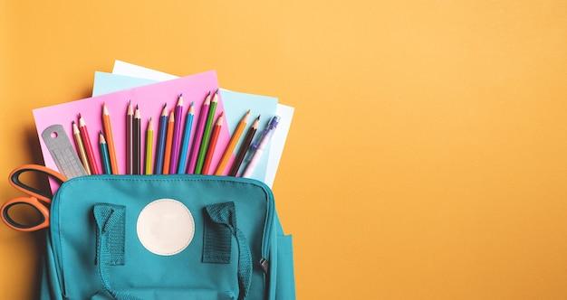 Retour à l'école. sac à dos bannière avec fournitures scolaires. vue de dessus et espace pour le texte. concept d'école ouverte.