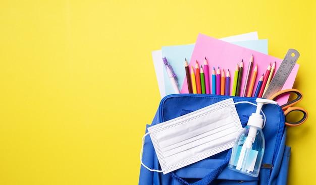 Retour à l'école. sac à dos bannière avec fournitures scolaires. vue de dessus et espace pour le texte. masque et gel d'alcool prévention covid-19 tout en allant au concept d'école ouverte.