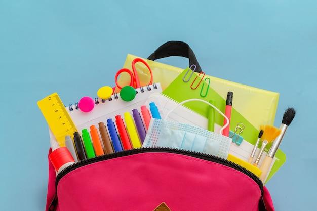 Retour à l'école sac à dos pour l'école ou le collège avec des fournitures scolaires colorées sur fond bleu
