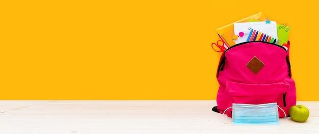 Retour à l'école sac à dos pour l'école avec des fournitures de bureau aux couleurs vives sur fond jaune