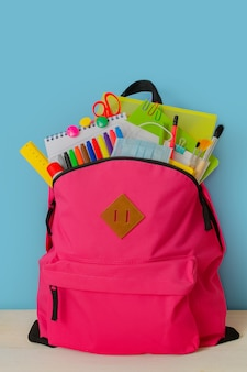 Retour à l'école sac à dos pour l'école avec des fournitures scolaires colorées lumineuses sur fond bleu