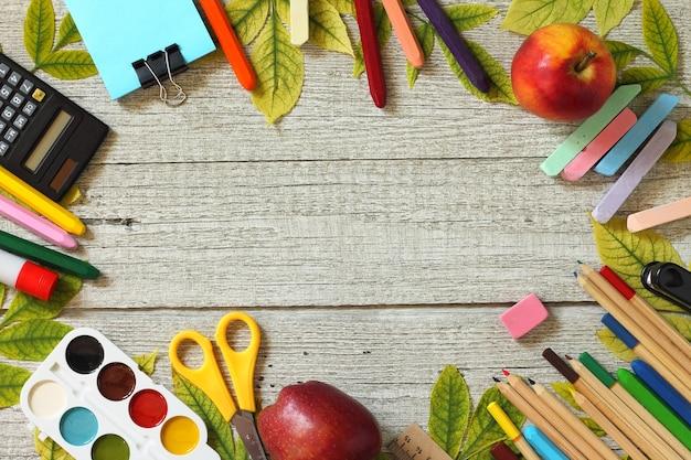 Retour à l'école table avec feuilles d'automne et différentes fournitures scolaires papeterie vue de dessus