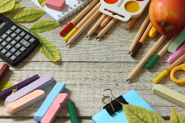 Retour à l'école table avec feuilles d'automne et papeterie de différentes fournitures scolaires
