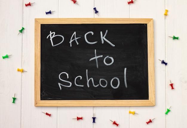 Retour à l'école tableau noir sur un fond en bois blanc, épingles de couleur. vue de dessus. espace de copie. notion d'éducation.