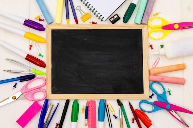 Retour à l'école tableau noir sur un fond en bois blanc, fournitures de couleur. vue de dessus. espace de copie. notion d'éducation.