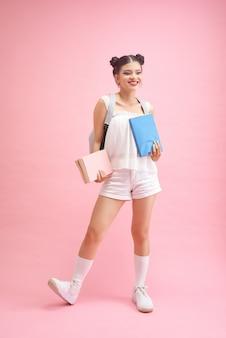 Retour à l'école. teen girl avec des livres sur un fond rose et jaune vif