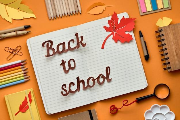 Retour à l'école texte sur ordinateur portable, mise à plat avec des fournitures et des feuilles de papier