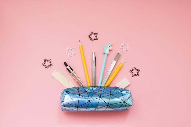 Retour à l'école. trousse avec des fournitures scolaires sur une table rose