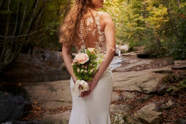 Retour gros plan de la belle jeune mariée tenant un bouquet sur le dos dans la forêt