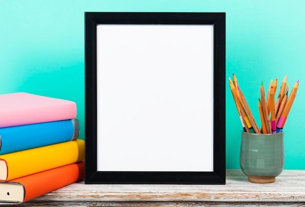 Retour à la notion d'école avec cadre blanc sur un bureau en bois ou une table avec une pile de livres