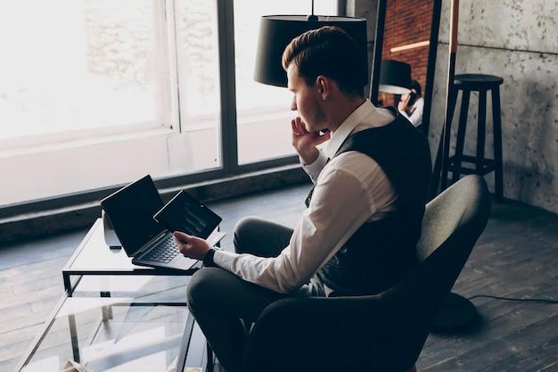 Retour portrait de gestionnaire caucasien adulte parler au téléphone avec son employé tout en tenant une tablette dans sa main contre une fenêtre.