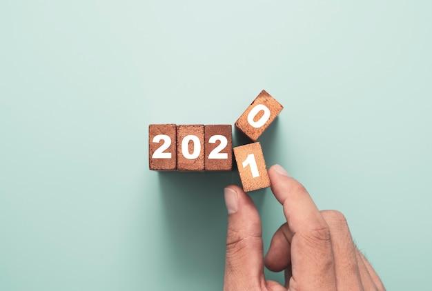 Retournement à la main du bloc de cubes en bois pour changer l'année 2020 à 2021