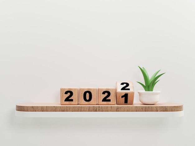 Retourner le bloc de cube en bois pour le changement 2021 à 2022 sur une étagère et une plante en bois pour la préparation joyeux noël et bonne année, rendu 3d