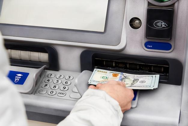 Retrait d'argent en dollars d'un guichet automatique.